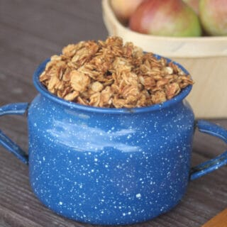 Applesauce Peanut Butter Granola piled into a blue tin cup with a basket of fresh apples behind it.