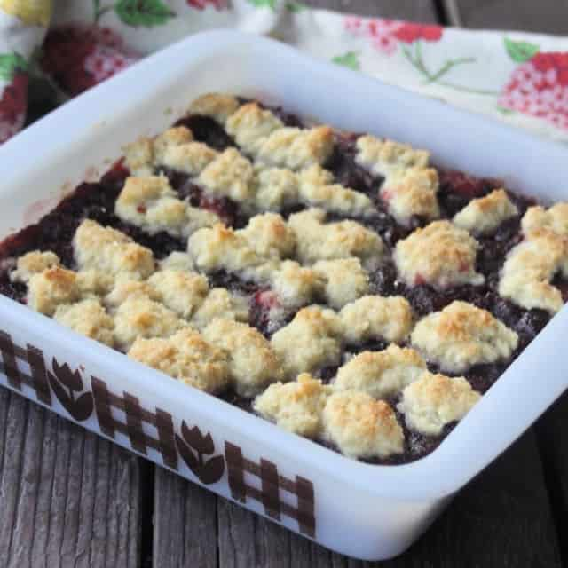 Chocolate cranberry bars in a white baking pan on a table with a napkin.