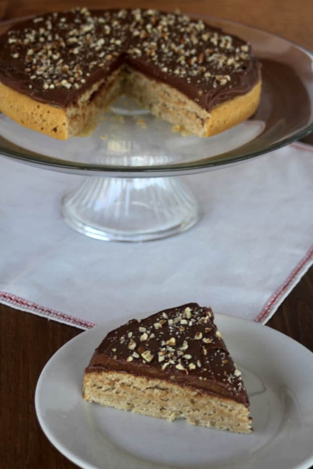 A slice of honey cake with chocolate honey frosting on a plate sitting in front of the entire cake on a cake pedestal.