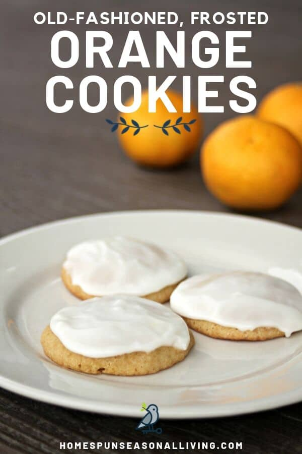 3 frosted orange cookies on a white plate