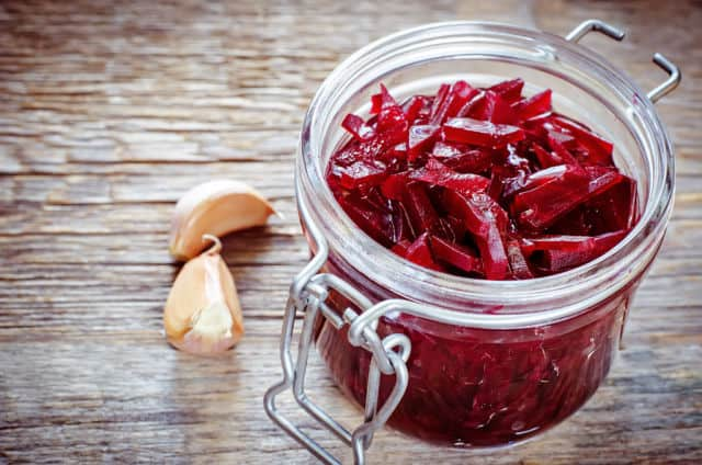 Shredded red beets in an open jar with cloves of garlic sitting next to it.