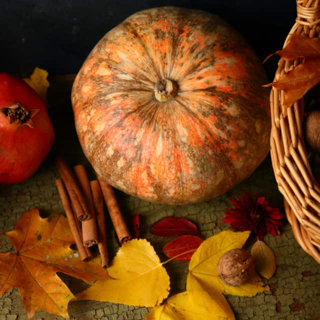 A pumpkin surrounded by fall leaves, cinnamon sticks, fruit, and nuts on a table.