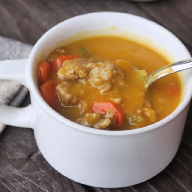 Hubbard Squash Sausage Soup in a white cup with spoon.