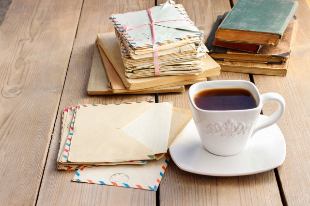 Stacks of letters and old books on table with a cup of coffee.