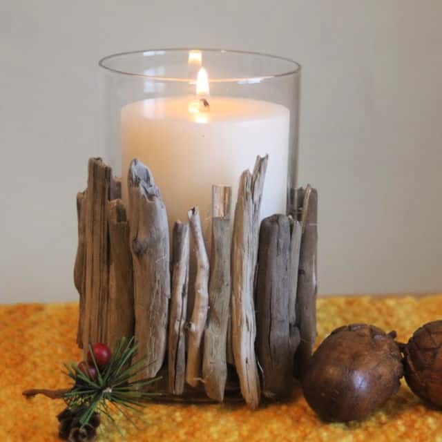 A lit candle in a driftwood candle holder on a placemat.
