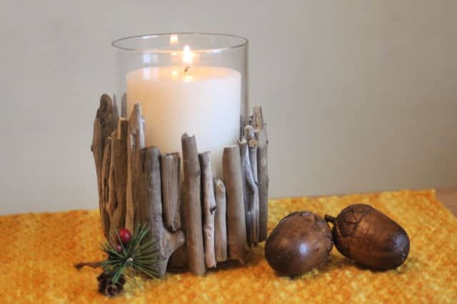 A glass candleholder decorated with pieces of driftwood sitting on an orange placemat surrounded by acorns.