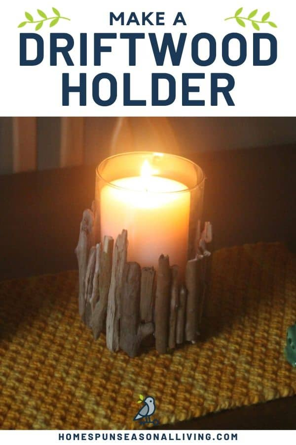 A darkened room with lit candle in a driftwood candle holder on a placemat.