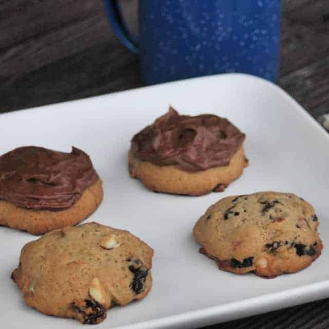Hermit cookies on a white plate with a blue tin coffee cup.