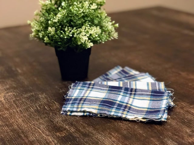 A stack of upcycled flannel hankies on a table with potted plant.