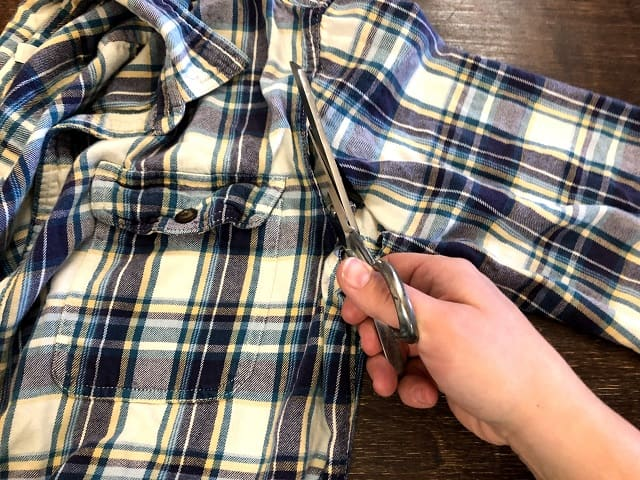 A hand with scissors cutting the sleeve off a flannel shirt.