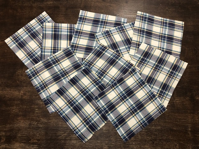 Squares cut from flannel shirts sitting on a table.