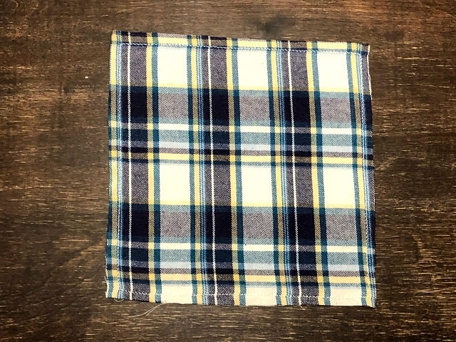 A square of flannel with a zigzag stitch sewn around the edges.