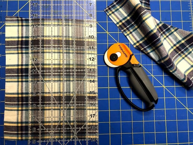 Pieces of flannel sitting on a cutting mat with a ruler and rotary cutter.