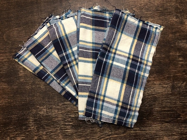 A stack of flannel hankies spread out into a fan pattern on a table.