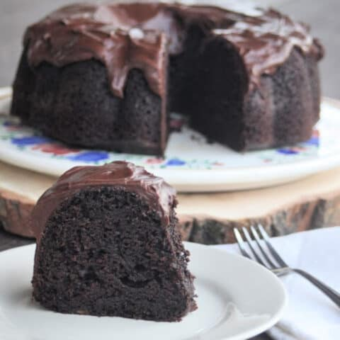 A slice of chocolate applesauce cake on a plate with a napkin and fork.