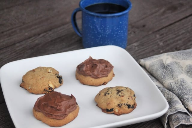 Hermit cookies on a white plate with a napkin and cup of coffee.