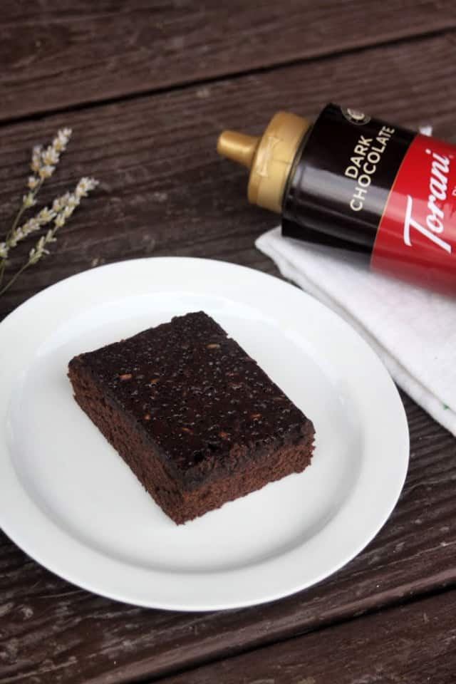 Lavender chocolate syrup brownie on a plate with dried lavender sprigs and bottle of chocolate syrup on a napkin.