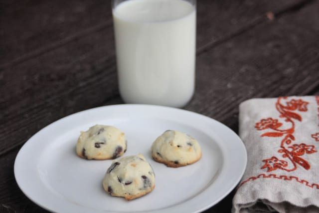 3 orange chocolate chip cookies on a plate with napkin and glass of milk.