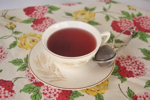 A cup of red tea on a saucer with tea ball.