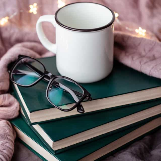A stack of books with eyeglasses and coffee cup on top.