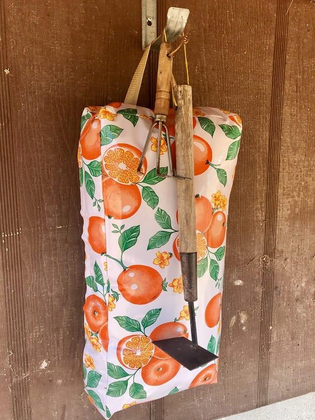 Hanging Garden Kneel Pad with oranges and garden tools