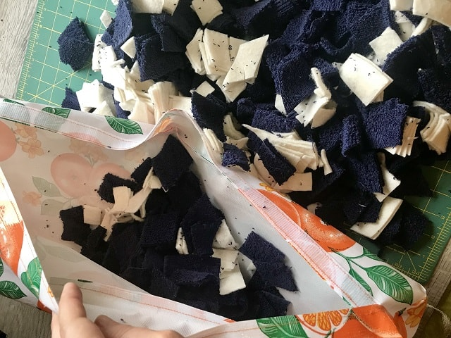 Sewn kneeling pad being stuffed with pieces of old towels.