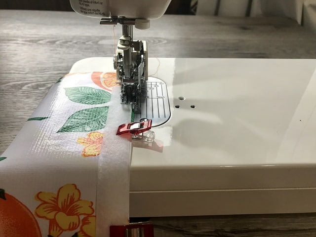 Sewing machine sewing hook and look onto oilcloth