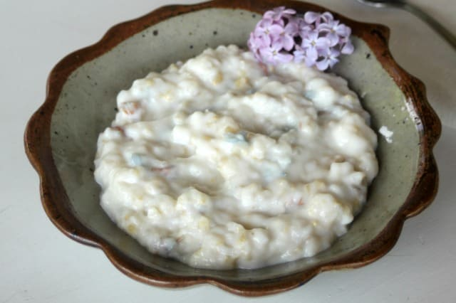 A bowl of lilac rice pudding garnished with a branch of fresh lilac blossoms.