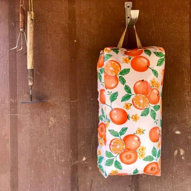 A garden kneeling pad hanging from a hook on a wood wall next to garden trowels.