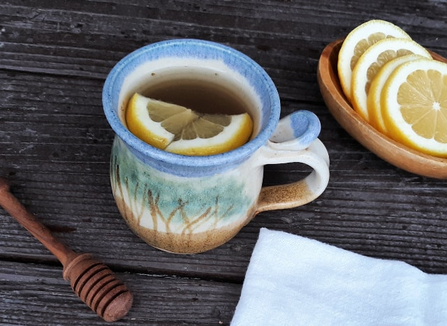 A cup of tea with lemon wedges surrounded by a honey dipper, white napkin, and wooden bowl of lemon slices.