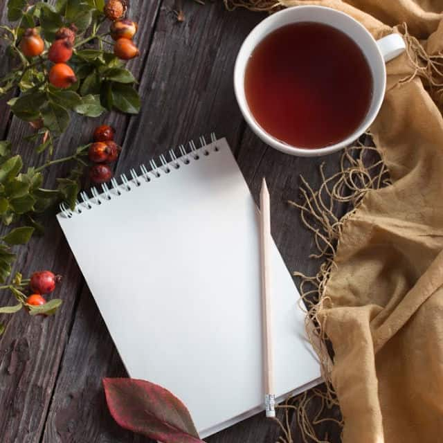 A wirebound tablet with pencil and cup of tea on a table with leaves and a scarf.