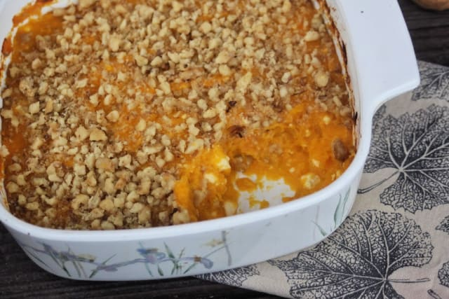 Pumpkin casserole in a pan with a spoonful missing exposing the inside.