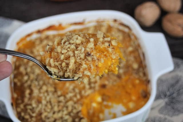 A spoonful of pumpkin casserole held above the pan.