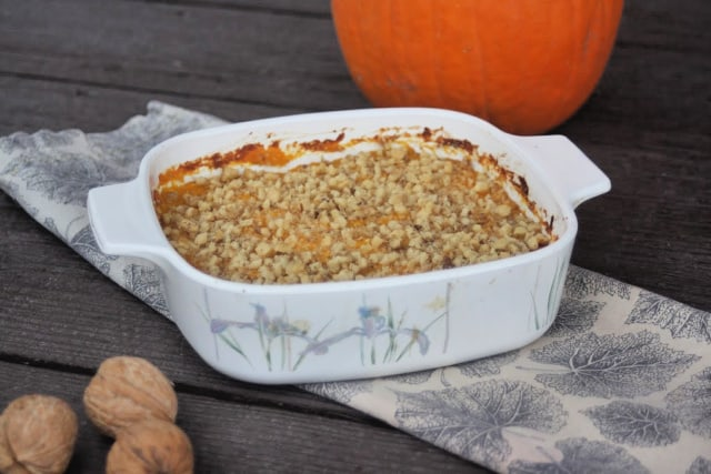 Pumpkin casserole in a baking dish sitting on top of a napkin surrounded by walnuts in shell and whole pumpkin.