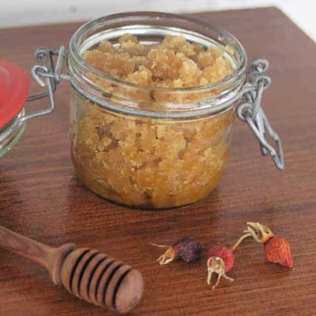 An open jar of rosehip sugar scrub on a table with honey dipper and dried rosehips.