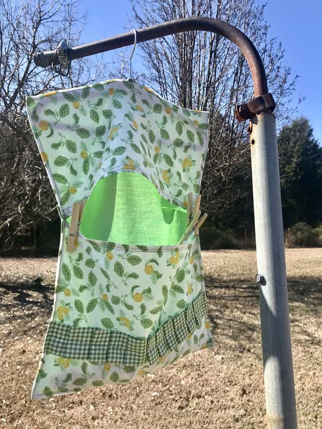 Clothespin bag hanging outside on rusty post in sunshine