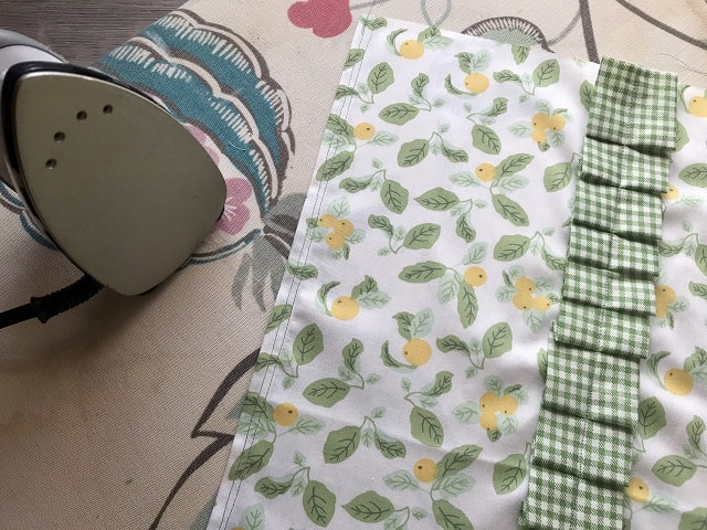 square of fabric with ruffle sewn on sitting next to iron on ironing board.