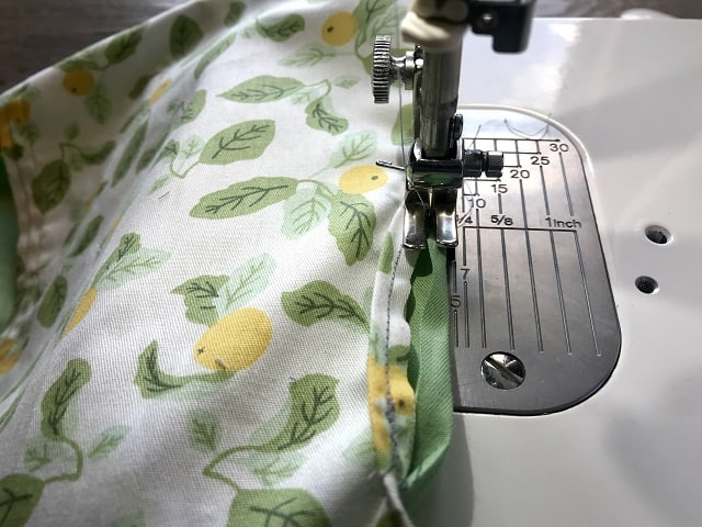 Sewing machine sewing around opening for hanger