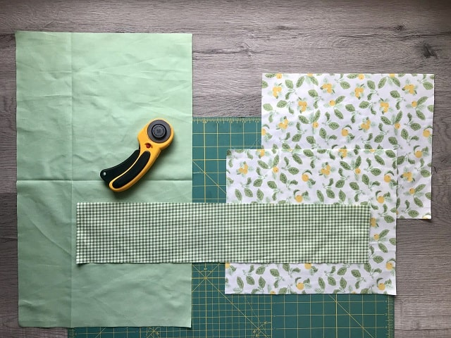 Pieces of fabric cut to size sitting on a cutting mat with rotary cutter.