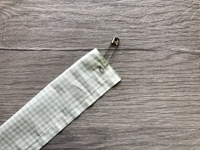 Tube of fabric with safety pin pinned to one end