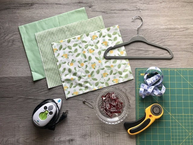 Green and yellow fabric, hanger, iron, sewing clips and rotary cutter