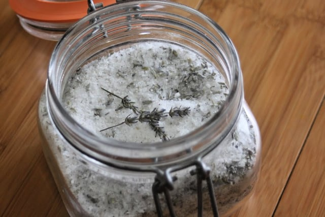 An open jar of bath salts with stems of dried lavender sitting on top.