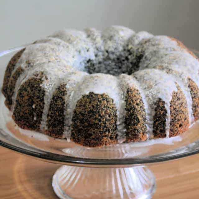 Glazed lemon poppy seed cake on clear glass cake stand.