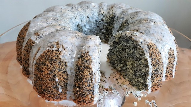 Glazed lemon poppy seed cake with a slice removed on glass cake plate.