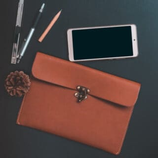 A leather satchel, pens, and smart phone on a dark table top with text overlay.