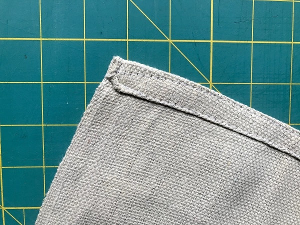 Corner of a drop cloth showing one edge hemmed and the other a selvage