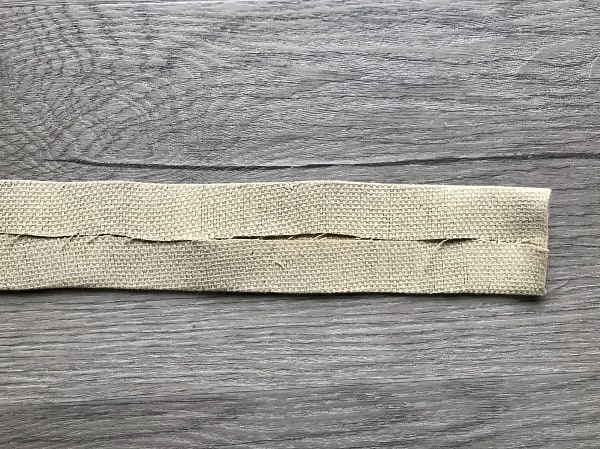 Top and bottom of strap folded to center and pressed