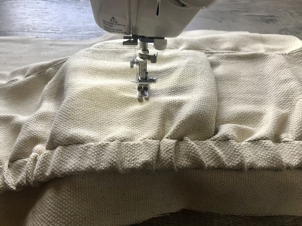 Sewing machine stitching vertically to form apron pockets