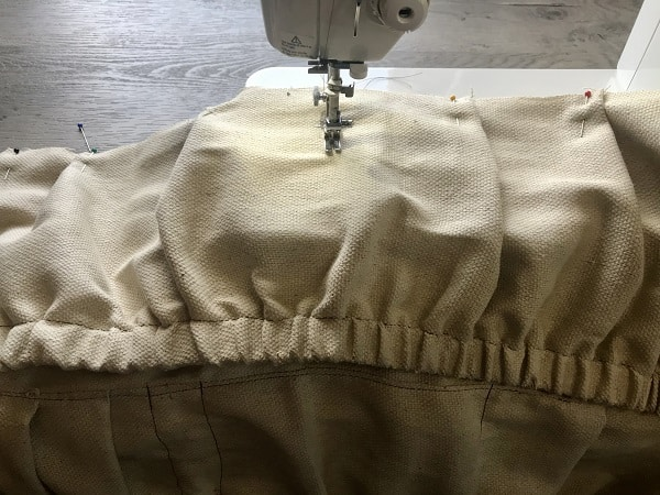 Sewing machine sewing pocket in center of bottom of apron