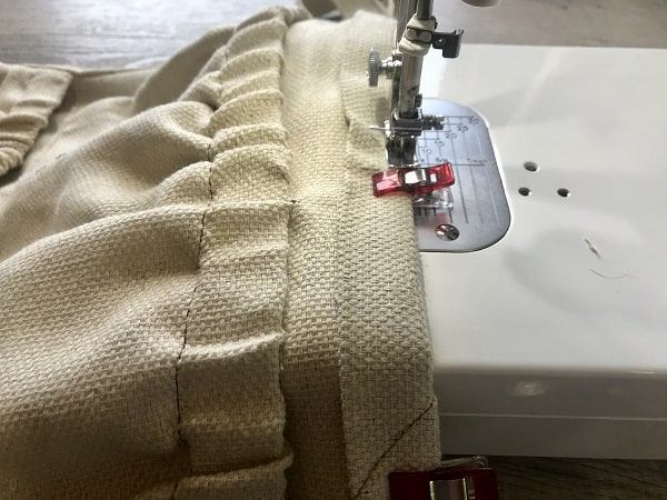 Sewing machine stitching top of strap to top of apron